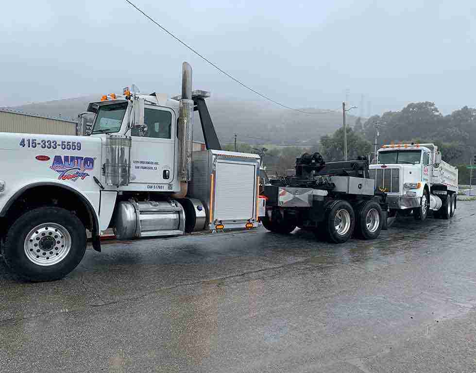 Gravel truck being towed by heavy duty tow truck SF CA | Auto Towing | 415-333-5559
