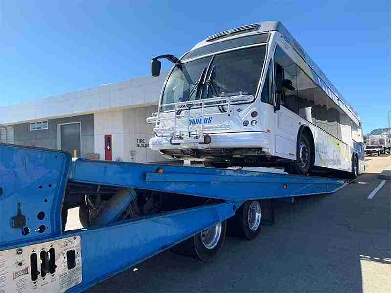 Tow Truck services towing city bus on a landoll in SF California